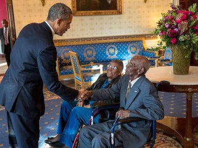 President Barack Obama greets Richard Overton, with Earlene Love-Karo, in the Blue Room of the White House, Nov. 11, 2013.