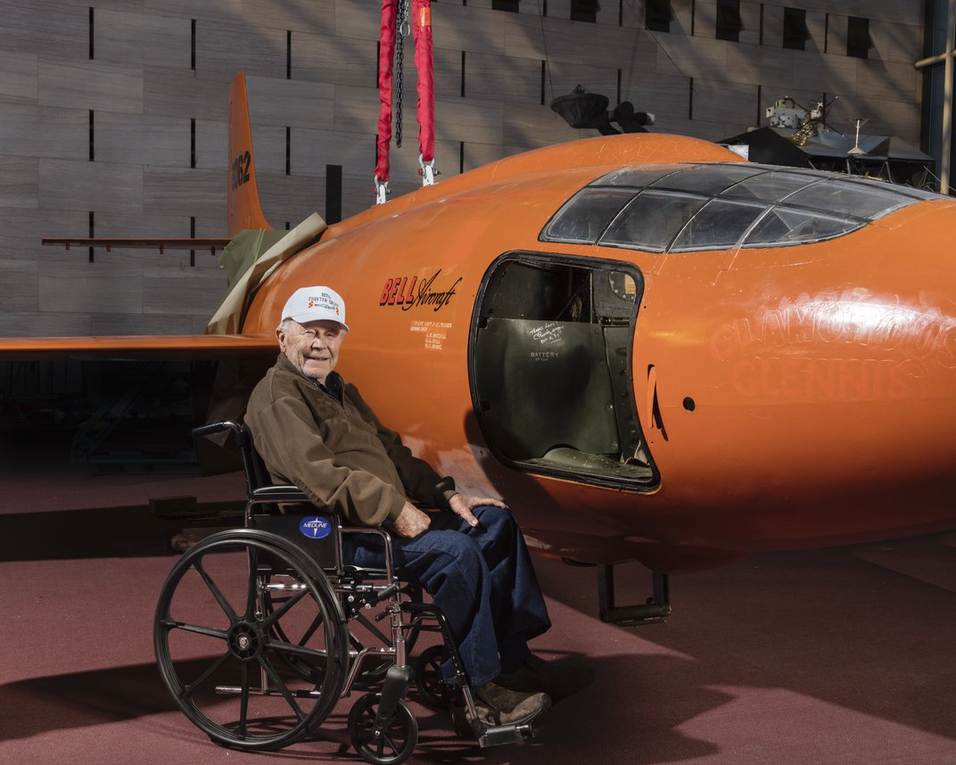 Chuck Yeager in wheelchair in front of orange Bell X-1.