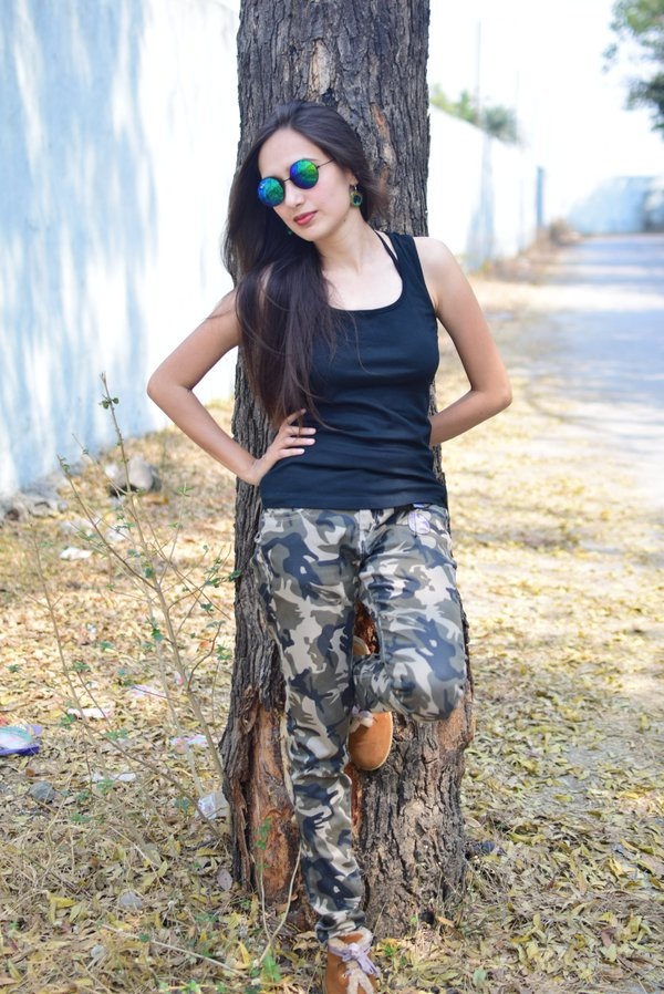 a girl standing near a tree thumbnail