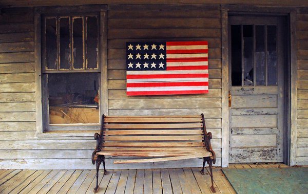 An American flag on an abandoned house thumbnail