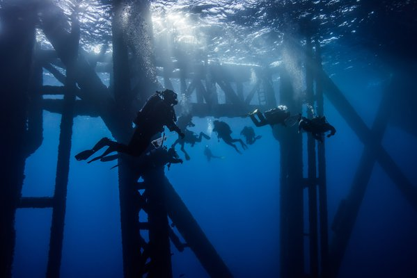 Group of Divers under an Oil Rig Platform. thumbnail