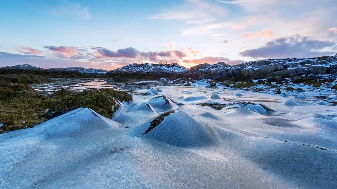 Rocky landscape covered in ice at sunrise