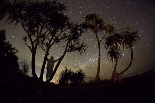 A man looks out on the Milky Way on a calm night in Palau, Micronesia. thumbnail