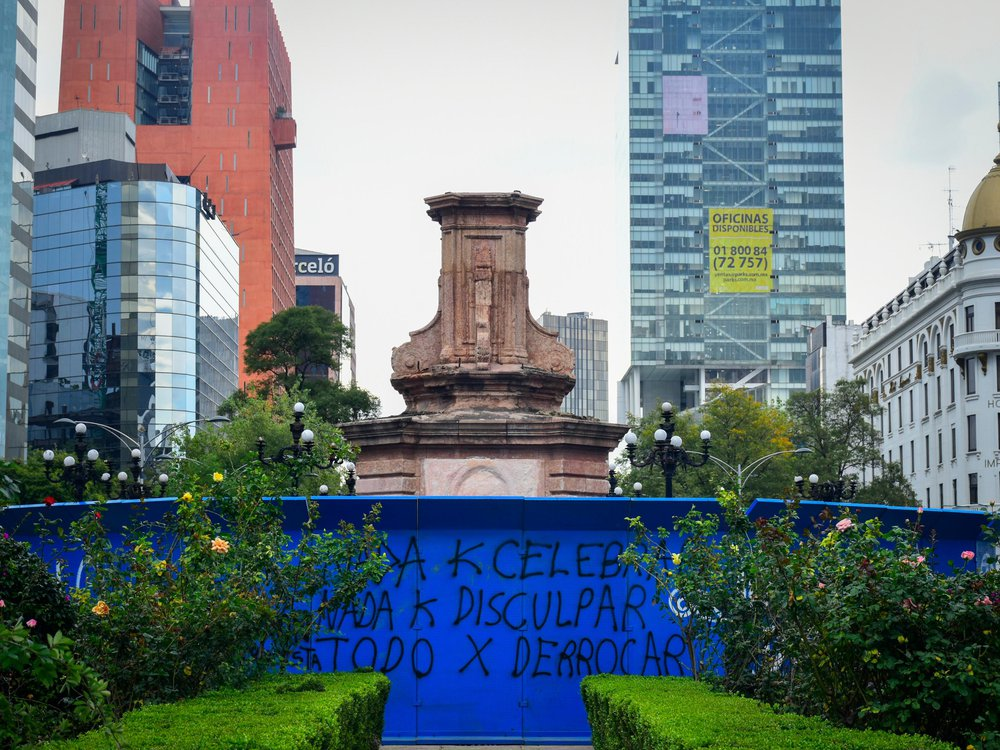 An empty pedestal stands, surrounded by tall buildings on all sides and a bright blue metal fence covered in graffiti