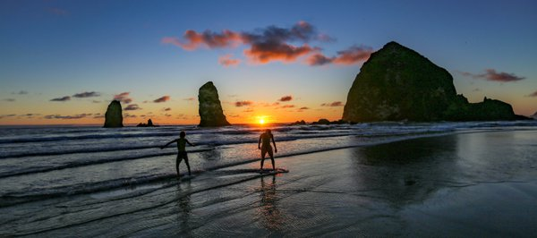 Boys skimboarding on Cannon Beach, Oregon thumbnail