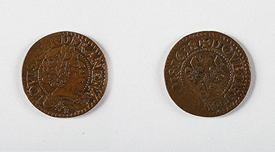 A team of Smithsonian scientists excavating the Hart Chalet site found a double tournois copper coin minted for French King louis XIII in 1634.  In pristine condition, it would have looked similar to this 1638 double tournois coin. (Images courtesy of the National Numismatic Collection, National Museum of American History, Smithsonian Institution. Image composite by Anna Torres)