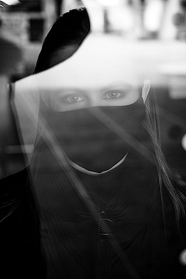 Masked girl looking through a shop window thumbnail