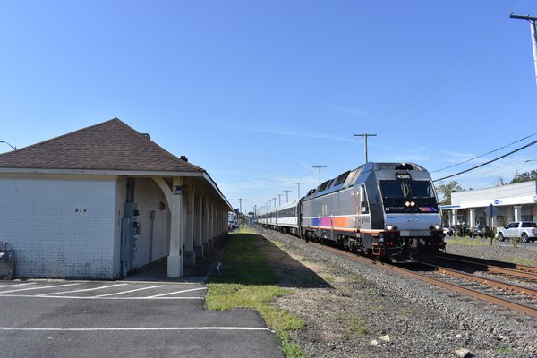 A train passing an old station building thumbnail