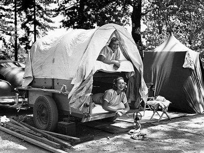 """Monon and Ottily Bayer, the daughters of Mr. and Mrs. Otto Bayer of Costamesa, California, pose in a small, """"bunk bed"""" trailer at their campground in the Shasta National Forest. California, August 1953."""