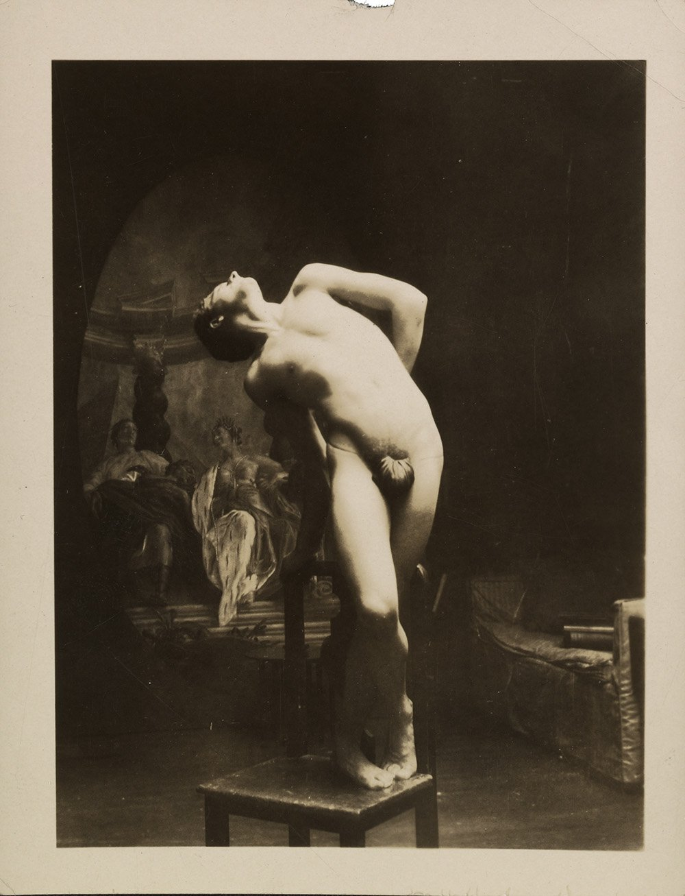 Photograph of an artists' model posing on a chair