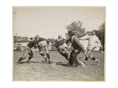 Photograph of John Steuart Curry sketching a football practice at the University of Wisconsin-Madison, 1936 or 1937 / unidentified photographer. John Steuart Curry and Curry family papers, 1848-1999. Archives of American Art, Smithsonian Institution.