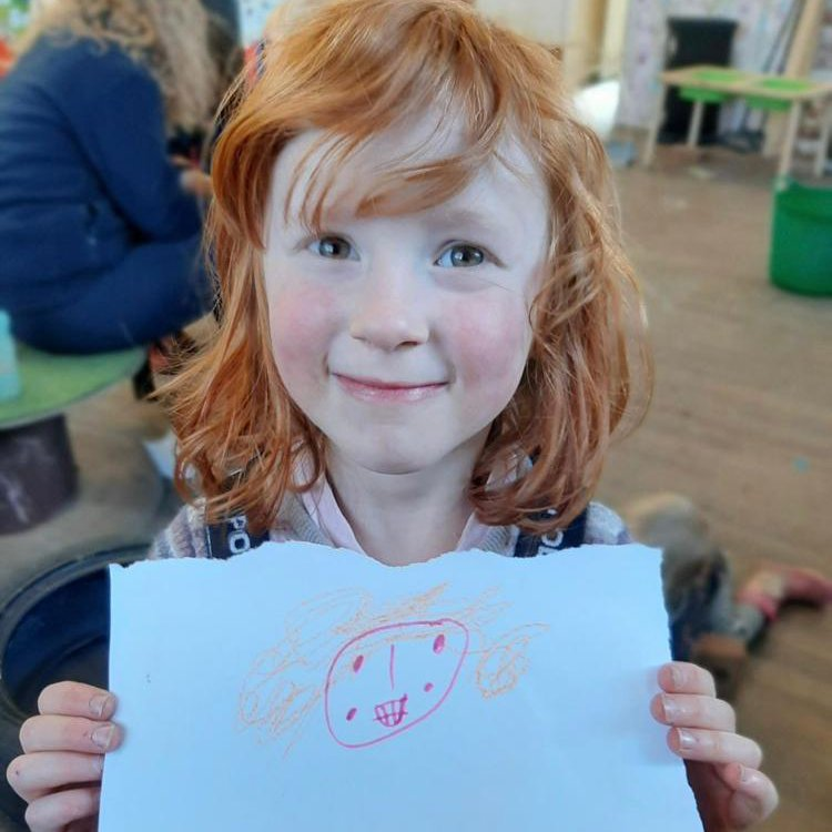 A pale, red-headed girl with bangs smiles and holds a piece of paper in front of herself, with what looks like a drawing of a person's smiling face and orange curly hair