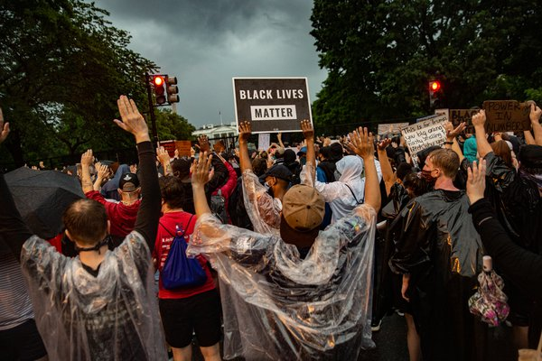 Black Lives Matter demonstrators raise their hands during a protest in the pouring rain outside of the White House thumbnail