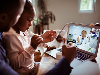 A father and his daughter engage in a video chat with their doctor.