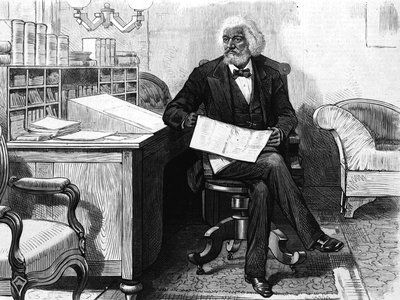 American orator, editor, author, abolitionist and former slave Frederick Douglass (1818-1895) edits a journal at his desk, late 1870s.