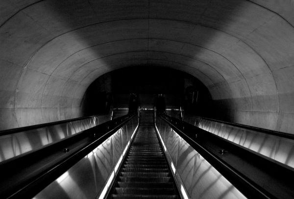A steep escalator descending into darkness. thumbnail
