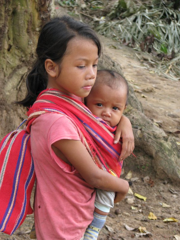 A young Bahnar girl carrying her smaller brother with a traditional scarf. thumbnail
