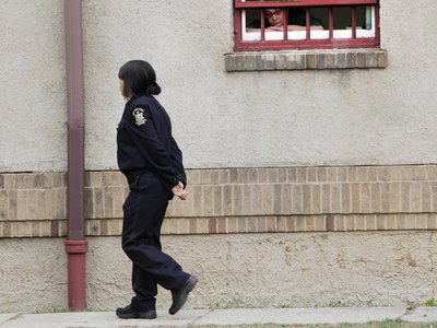 A woman peers out of a residential complex at the women-only Taconic Correctional Facility in Bedford Hills, New York, in 2012.