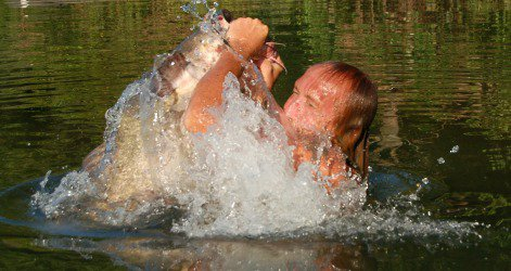 David Baggett, famed among noodlers, explodes from the water with a giant catfish in his hands.