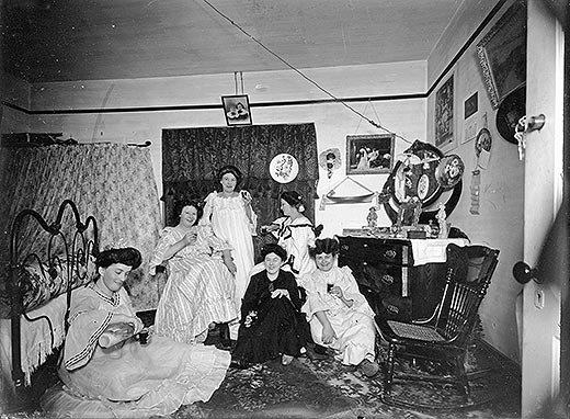 Women posed together with drinks in hand in bedroom