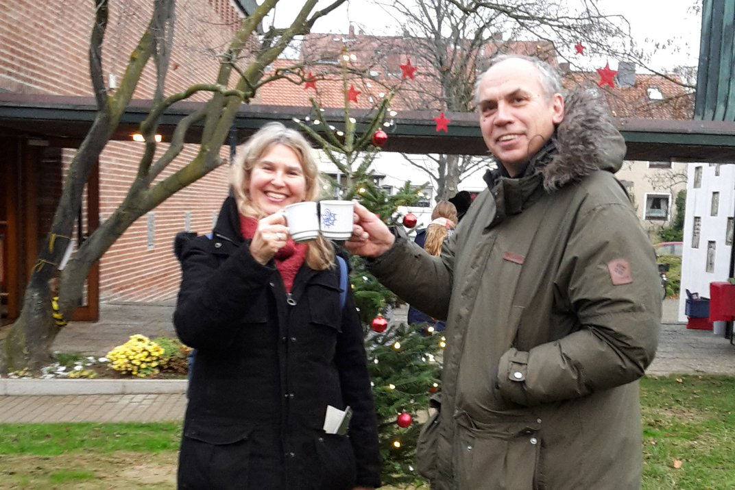 A couple smiles and clinks mugs of mulled wine.