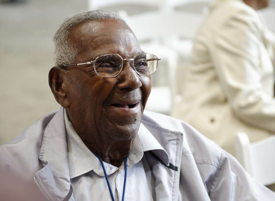 A close-up of Brooks, a black man with glasses and gray hair, smiling and wearing a white collared shirt and overcoat; he is sitting down and uses a wheelchair (not pictured)
