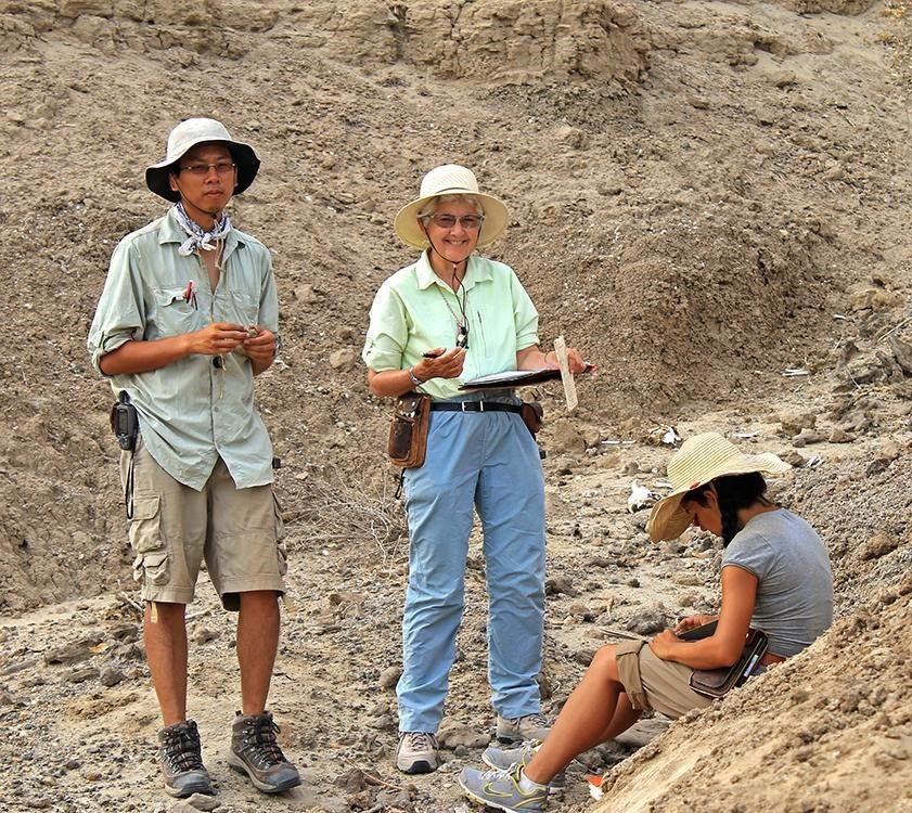A group of people standing in a desert.