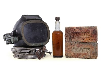 A bottle of whiskey, a diving helmet and bricks recovered from the wreck of the SS Politician, which sank off the coast of Scotland in 1941.
