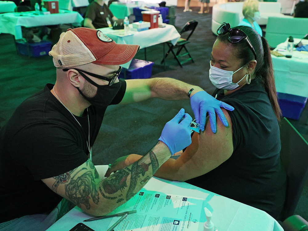 A woman in a black shirt and sunglasses gets a vaccine from a man in a black shirt and red baseball cap, both sitting at a white table and wearing masks