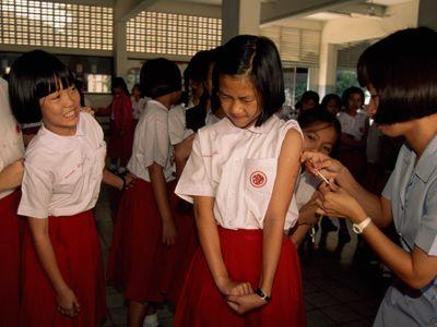 School girls line up to receive vaccinations between classes.