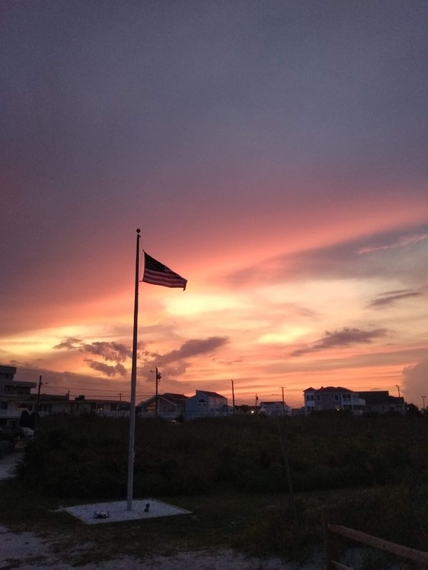 Perfect combination of a waving American flag and fiery sunset sky thumbnail
