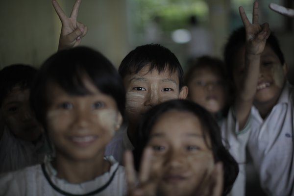 A group of Burmese students crowd together for a portrait in a Mandalay classroom.  thumbnail