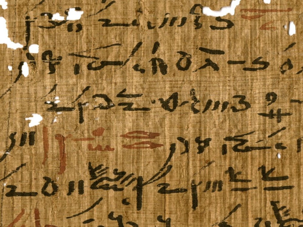 A yellow-orange papyrus sheet, with some small holes, with elongated handwritten black hieroglyphic script, with small sections every few lines written in faded red ink