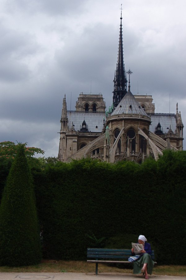 Woman reading paper behind Notre Dame thumbnail