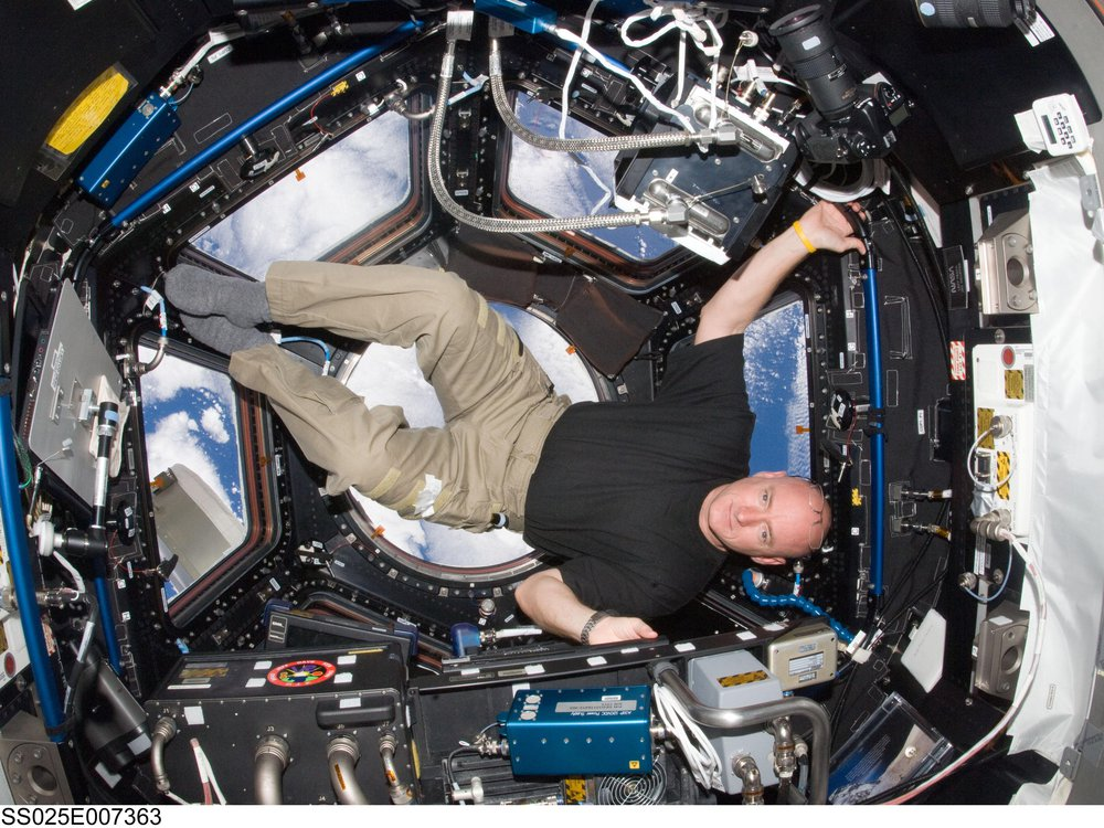 Astronaut Scott Kelly is sideways in the Cupola of the International Space Station