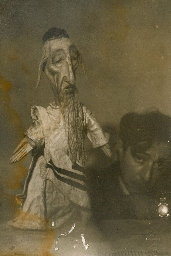 A sepia toned photo shows a handmade puppet of a Rabbi. In the background, a man with cropped, dark hair crouches down holding the puppet.