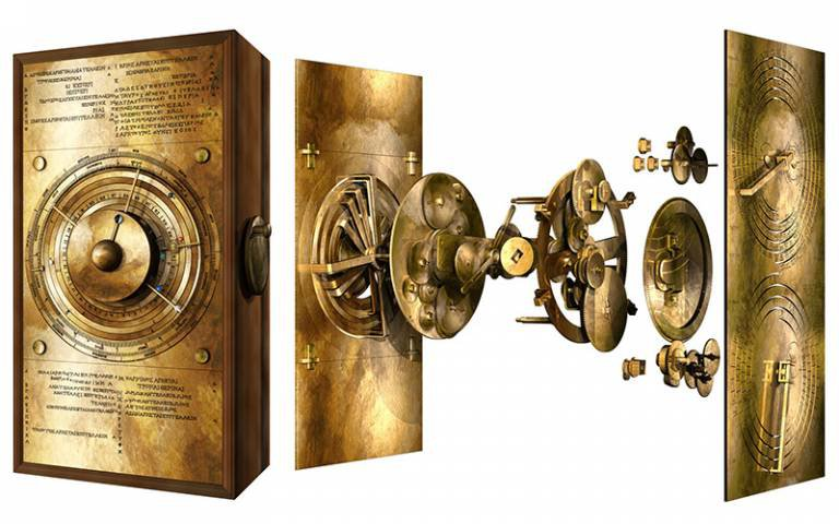 A model of a gleaming golden box, made of bronze, with detailed inscriptions, jeweled markers for planets and a clock-like face with complicated gear mechanisms behind