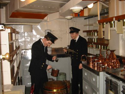 """This diorama shows a sailor receiving his """"daily tot."""" It was even mixed according to custom: on a """"scuttled butt"""" with an officer overseeing the mixing."""