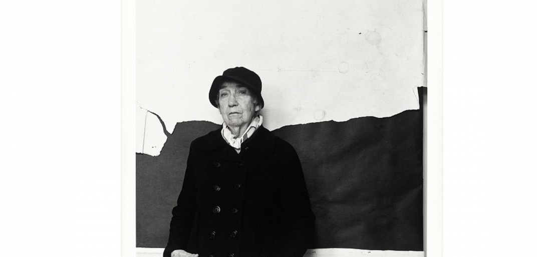 A black and white photograph of a woman in a black coat and black hat against a black and white back drop.