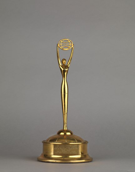 A gold award. There is a circular base with engravings on the front and a slim figure holding up a flat circle with lines running across it.