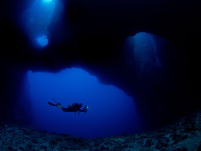 A scuba diver swims in the coral reefs of Palau. Beneath the depths that humans can dive, natural wonder and a better understanding of our planet awaits.
