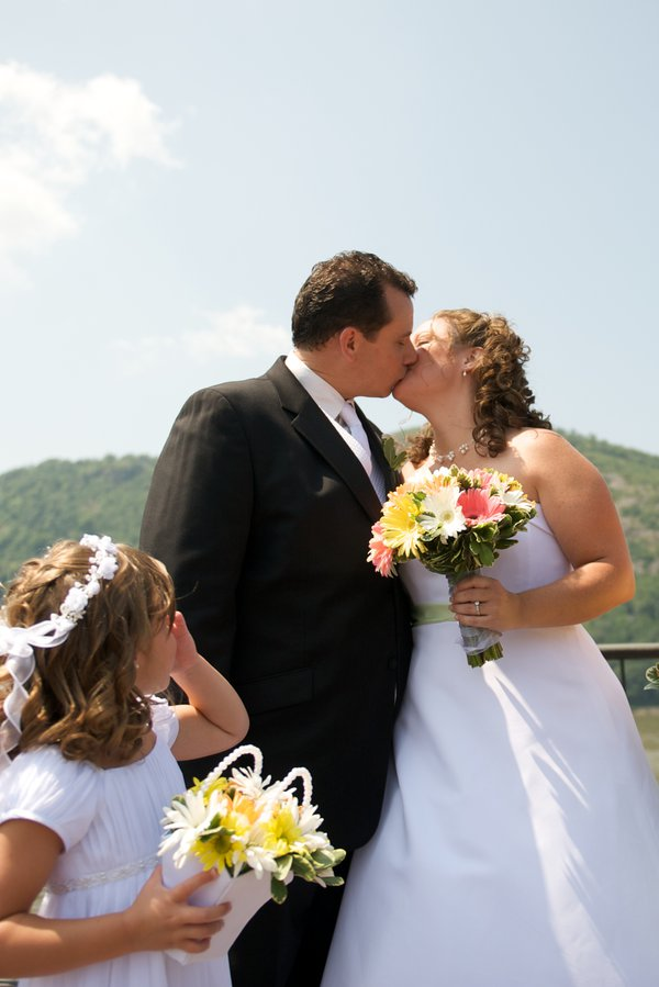 Groom and Bride kissing while the flower girl admires thumbnail