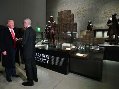 "President Trump talks to Smithsonian Secretary David Skorton in front of the ""Paradox of Liberty"" exhibit."