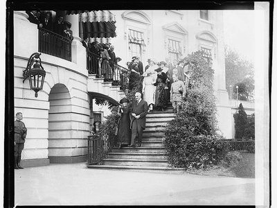 Marie Curie and President Warren Harding walk down the White House steps arm in arm in 1921.