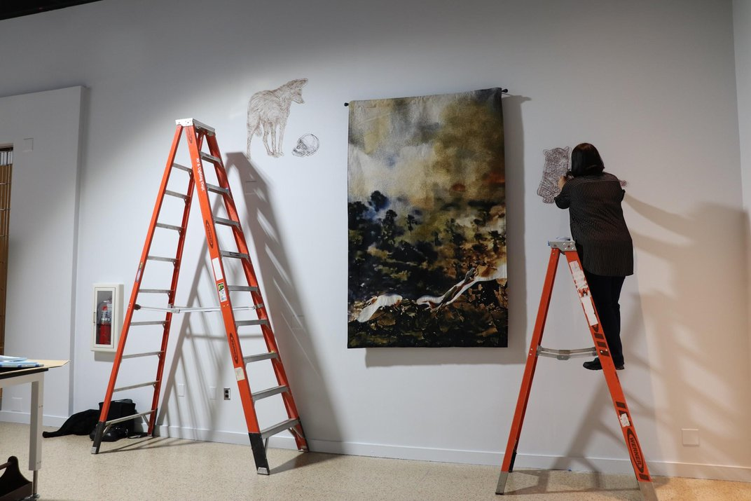 Artist on a ladder nailing string art to a white wall next to a tapestry
