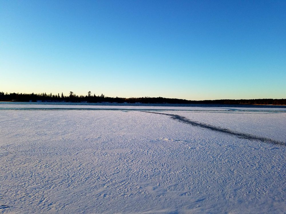 A photograph of a frozen lake landscape with trees on the distant horizon