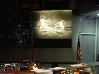 NASA Mission Control during the Apollo 11 moonwalk, with the live broadcast from the lunar surface on the screen.