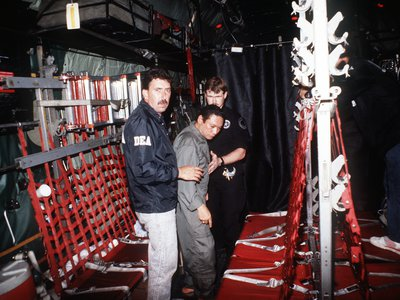 Manuel Noriega is escorted onto a U.S. Air Force aircraft by agents from the U.S. Drug Enforcement Agency (DEA) in 1990.