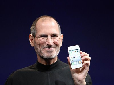 Jobs holds up an iPhone 4 at a tech conference in 2010.