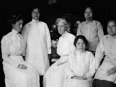 Tien Fuh Wu (standing in the back, on the left) and Donaldina Cameron (seated, center) with a group of women who may have been Mission Home staffers.